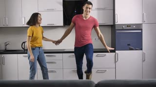 Sweet and funny young adults couple in casual outfits having fun dancing together in the kitchen at home. Creative hipsters making dance moves and enjoying together in domestic interior. Slow motion.