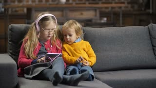 Sweet little siblings sitting together on sofa in domestic room and using tablet pc. Cute blond hair brother and sister in headphones and glasses talking, surfing the net, choosing a cartoon to watch