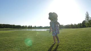 Sweet little toddler girl with down syndrome walking during sunset on green grass meadow barefoot. Adorable child throwing down summer hat and enjoying the walk in nature in park. Slow mo. Steadicam