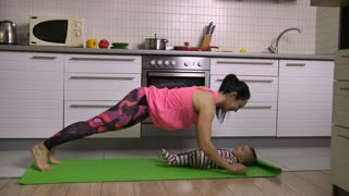 Sweet mother and child making sport together in the kitchen at home. Little baby lying on yoga mat while sporty woman kissing him each time doing plank and push-up excercise. Dolly shot.