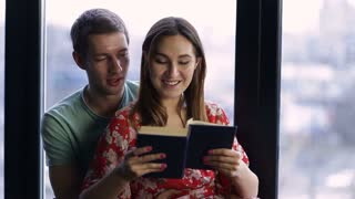Sweet young couple reading a book together at home
