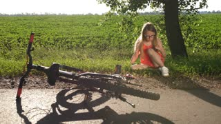 Teenage girl had biycle crash while riding bike in countryside. Blonde teen fell of the bicycle, sitting or road side, blowing air on injured dirty knee trying to soothe the pain.