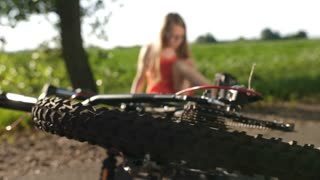 Teenage girl sitting on road in countryside after bicycle accident. Rack focus from spinning bike wheel to blonde teen schoolgirl in glasses blowing air on injured dirty leg trying to relieve pain.
