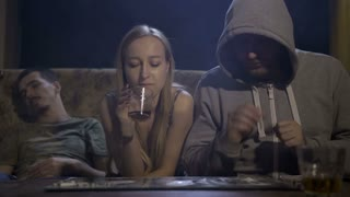 Three young addicts sitting on sofa near the table at night. Man in a hooded shirt snorting cocaine and offering a woman. Female refusing cocaine, she quit. Another male lying on couch after overdose