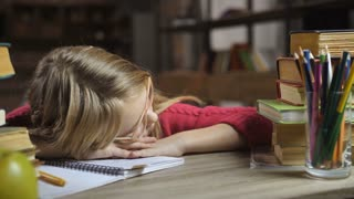 Tired blond hair girl sleeping at the desk at home