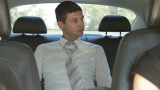 Tired businessman relaxing at the backseat of car