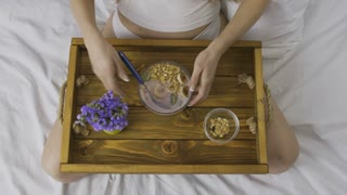 Top view midsection of woman eating healthy breakfast at home in bed. Female with wooden tray on lap enjoying yogurt with granola and fruits. Healthy lifestyle, diet, weight loss, organic food concept