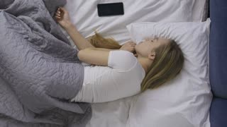 Top view of positive young woman waking up, smiling, stretching in bed and taking her cellphone. Happy girl in white t-shirt wakes up in the morning and starts using her smartphone