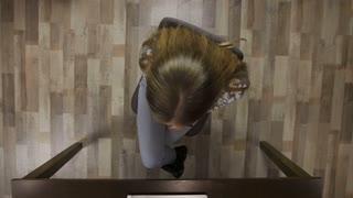 Top view of stressed, concentrated female office employee spinning on office chair at the table. Young business worker in eyeglasses thinking, generating ideas and squeezing anti stress relieve toy.