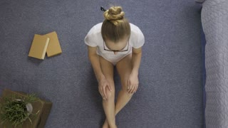 Top view of teenage girl sitting in lotus pose and meditating in the morning on the floor near bed. Young woman in eyeglasses relaxing and meditating in white underwear after she woke up at home.