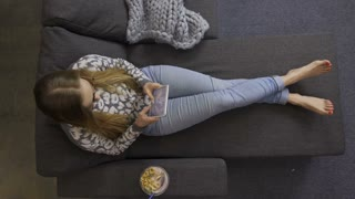 Top view of young woman sitting on cozy sofa with legs outstretched and using touchpad in domestic room. Comfortable female in jeans scrolling and typing on tablet pc with healthy yogurt breakfast
