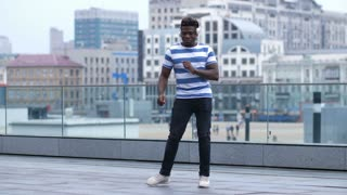 Trendy african american hipster man in white headphones enjoying the sound of afrobeat and making dance moves outdoors over cityscape background. Flexible man dancing freestyle dance in city street.