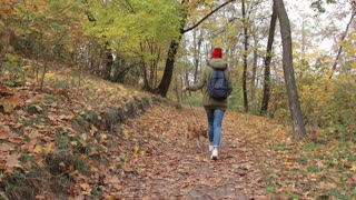 Trendy hipster girl walking the dog in autumn park