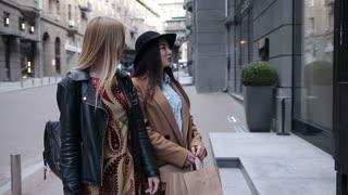 Two excited elegant women looking in shop window