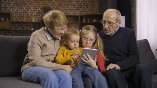 Two generations using digital touhpad together at home on the sofa. Cute blond hair grandchildren surfing the net, browsing pages and talking together with grandparents in domestic room. Dolly shot