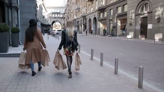 Two happy girlfriends on shopping with bags
