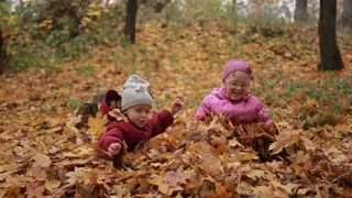 Two happy kids throwing fallen leaves up in fall