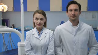 Two medical staff coworkers in white lab coats at doctor's office looking at camera and smiling with radiant toothy smiles. Handsome young male doctor and beautiful female dentist smiling