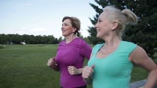 Two pretty senior females joggers training in park