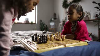 Two smart little girls playing chess on bed