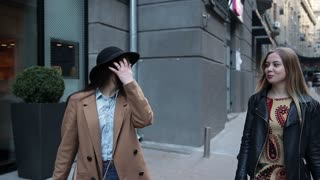 Two young women with shopping bags walking in city