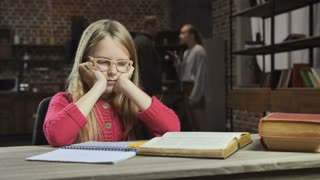Upset girl studying while her parents fighting