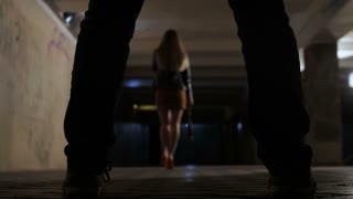 View from between male criminal legs, back view of beautiful young woman walking through dark underpass at night alone. Killer chasing his female prey, while going alone in city