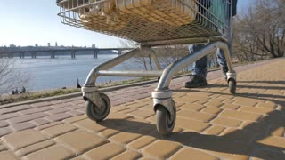 Wheels of shopping cart, which homeless man pushing down the road on a sunny autumn day. Beggar's legs walking with cart on the river bank. Homelessness and social issues concept. Steadicam shot.