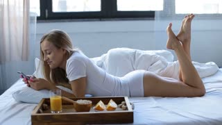 Woman eating breakfast in bed whilst using phone