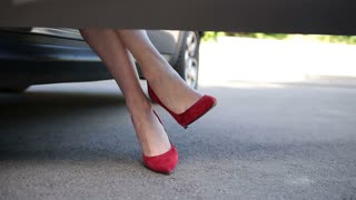 Woman in red high heels sitting in parked car