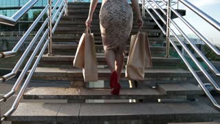 Woman legs walking on stairs with shopping bags