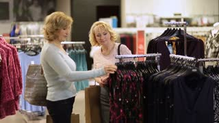 Woman selecting apparel while shopping for clothes