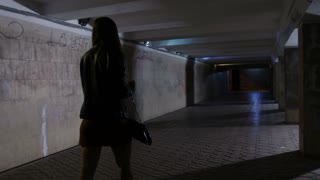 Woman walking alone at night in dark tunnel underpass. Male in hooded jacket robbing female and stealing her bag. Criminal taking the bag and running away to darkness. Steadicam stabilized shot
