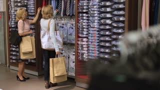 Women choosing necktie during apparel shopping