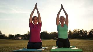 Women yoga meditating in lotus pose hands overhead
