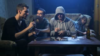 Young addicted people hanging out together in a dark room at night. Friends smoking, drinking alcohol, making lines of cocaine on the table. Female addict passed out after overdose on the couch.