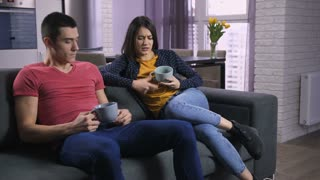 Young adults couple sitting on the sofa watching TV and arguing about what television channel and program to watch. Irritated boyfriend and girlfriend fighting over remote control at home.