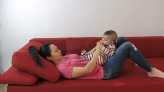 Young attractive mother playing with her adorble baby son's feet at home. Middle aged smiling woman lying on red sofa, holding baby on her lap and playing with little infant's feet at home. Side view.