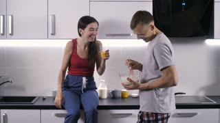 Young attractve couple in good mood spending great time together in the morning. Sweet young people laughing, talking, joking and laughing while man preparing breakfast for his girlfriend.