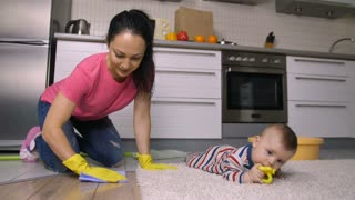Young beautiful latin mother scrubbing kitchen floor in rubber gloves on her knees while her cute baby boy playing on the carpet. Pretty mom entertaining her child while cleaning the house. Dolly shot