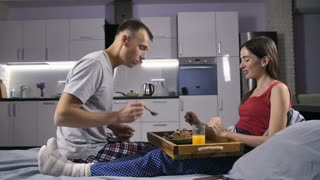 Young beautiful romantic couple sitting in bed in pajamas in the morning, eating homemade pancakes together after caring husband served them to his lover in bed. Happy couple enjoying and laughing