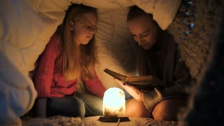 Young blond mother and her teenage daughter in eyeglasses siting in bed under blanket with a warm lamp and reading bedtime stories and fairytales together at night. Happy family relaxing together