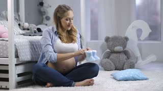 Young blonde expecting mother sitting in children's bedroom and playing with cute little blue baby shoes, stepping them on the carpet. Pregnant female dreaming about baby, expecting new family member