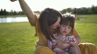 Young brunette mother and beautiful little toddler daughter with down syndrome sitting on green grass lawn and laughing together. Happy moment of sweet joyful family. Slow moton.