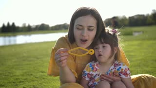 Young brunette mother and special needs little toddler daughter sitting on green grass lawn and blowing soap bubbles together. Mom and daughter enjoying and together in summer on meadow