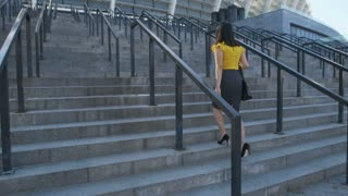 Young business woman in pencil skirt walking up the stairs to business office center to work. Back view full length asian businesswoman climbing stairway in high heels, going to workplace. Steadicam