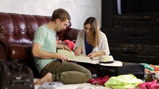 Young couple planning vacation trip with map