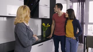 Young couple talking to senior female real-estate agent near kitchen studio in modern apartment. Positive family willing to rent a flat. Husband and wife open kitchen drawers while talking to realtor.
