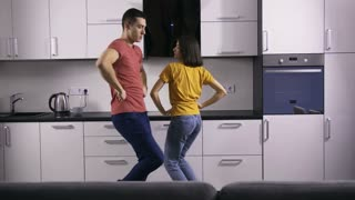 Young creative hipster couple dancing together in the kitchen at home. Fancy funny young people being silly and enjoying together celebrating after moving to their new house. Newlyweds in new home.