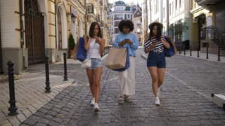 Young diverse women walking in city center holding smartphones and shopping bags. Stylish shopper girlfriends smiling and looking into mobile phones while fashion shopping together. Full length shot